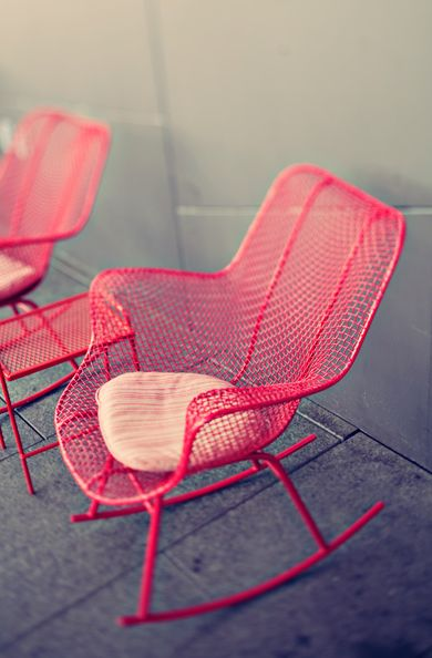Colourful Hot Pink metal mesh rocking chairs, they would look as fabulous inside as in a garden!