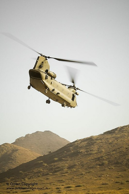 A Royal Air Force Chinook helicopter over the mountainous terrain of the North African desert in preparation for deployment to Afghanistan.