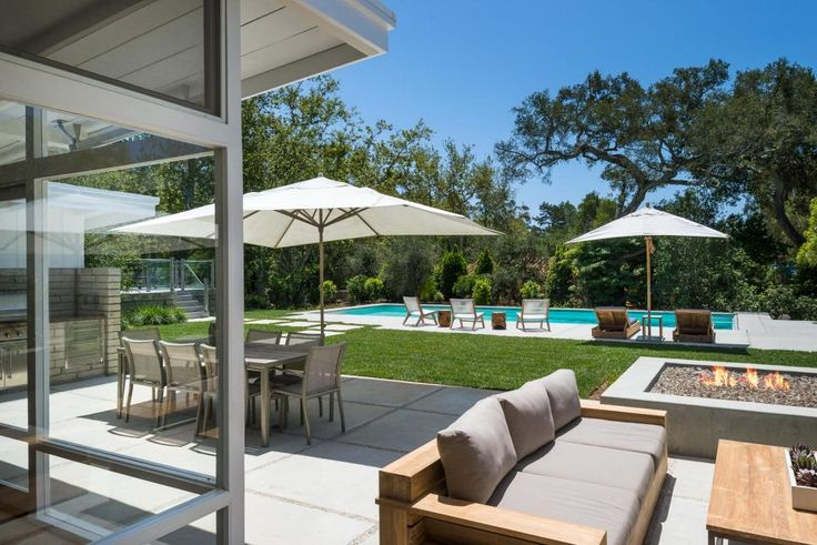 The patio view from this midcentury modern home is stunning: A pool in the distance is lined with lounge chairs for sunning and surrounded by the endemic trees of the region for privacy. Near to the home, an outdoor dining table and living area provide ample space for entertaining, and a fire pit adds warmth and pizzazz.