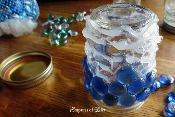 Applying silicone sealant adhesive to garden art treasure jars