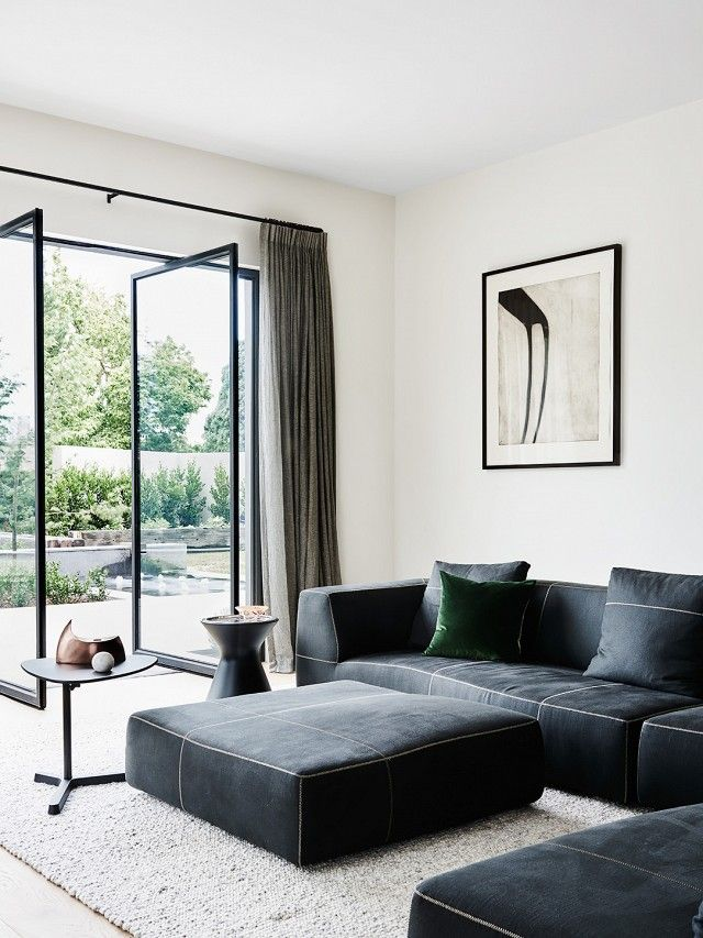 A velvet throw pillow in forest green is just the right touch of color in this monochrome living room.