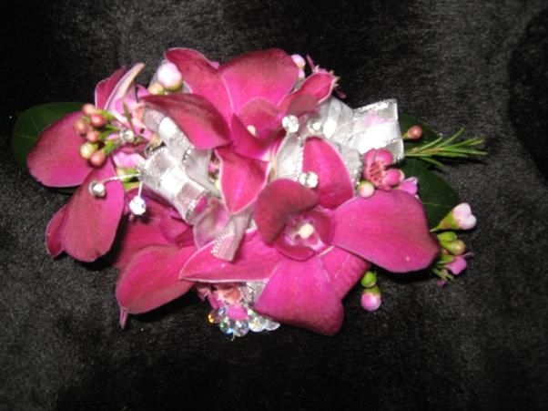 These elegant purple orchids are accented with some faux diamonds for some extra sparkle to match the special wrist band.
