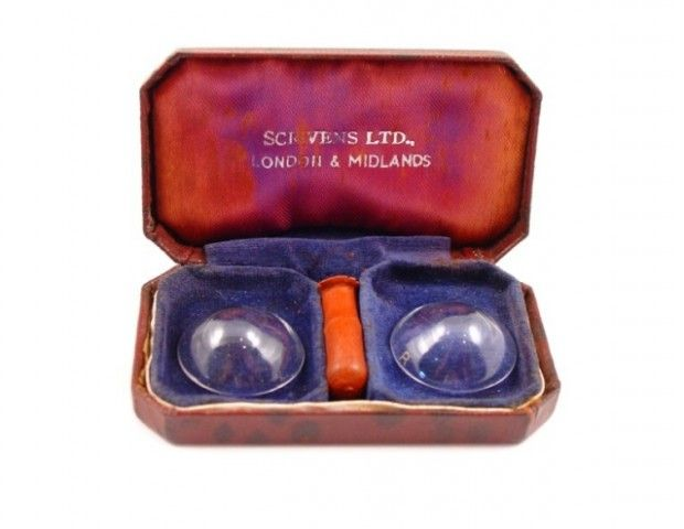 These large hard contact lenses from 1940 were called 'haptic' or 'scleral' lenses because rested only on the sclera or white outer portion of the eye.    The un-sterile case is fitted with blue velvet and contains the original rubber suction holder. The red silk lined lid is marked Scrivens Ltd London and Midlands.