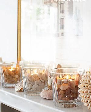 "Display pretty pebbles, or little rounded glass, in charming tealight holders. Place a small, shallow tealight holder at the bottom of a sturdy glass tumbler then arrange small pebbles & glass pieces around it. Place a tealight in a second holder & place on top of the first one (if you have lots of pebbles, you could put some pebbles in instead of the first holder, to raise up the second one). Continue adding small pebbles up to the top of the tealight ("",)"