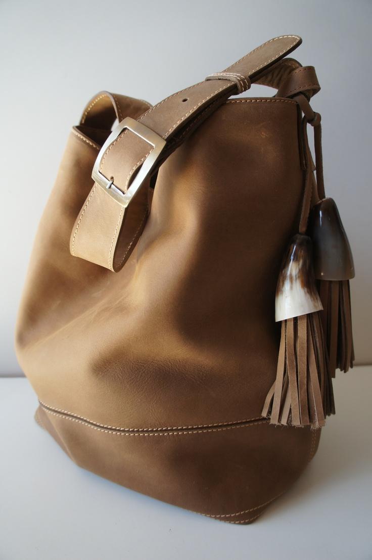 Cartera tipo bolso, color suela, con acacesorios de cacho y pompones de cuero