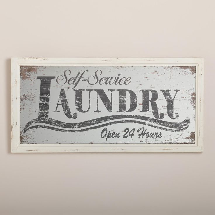 """Our """"Self-Service Laundry"""" Printed Mirror pops with retro typography printed on mirrored glass with an antiqued finish. Complete with an off-white wooden frame and a saw tooth hanger on the back, it's ready to hang by the washer and dryer."""