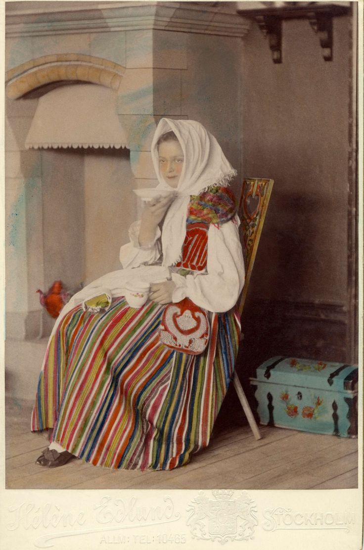 En kvinna klädd i dräkt från Östra härad i Småland sitter i ett kök och dricker kaffe.