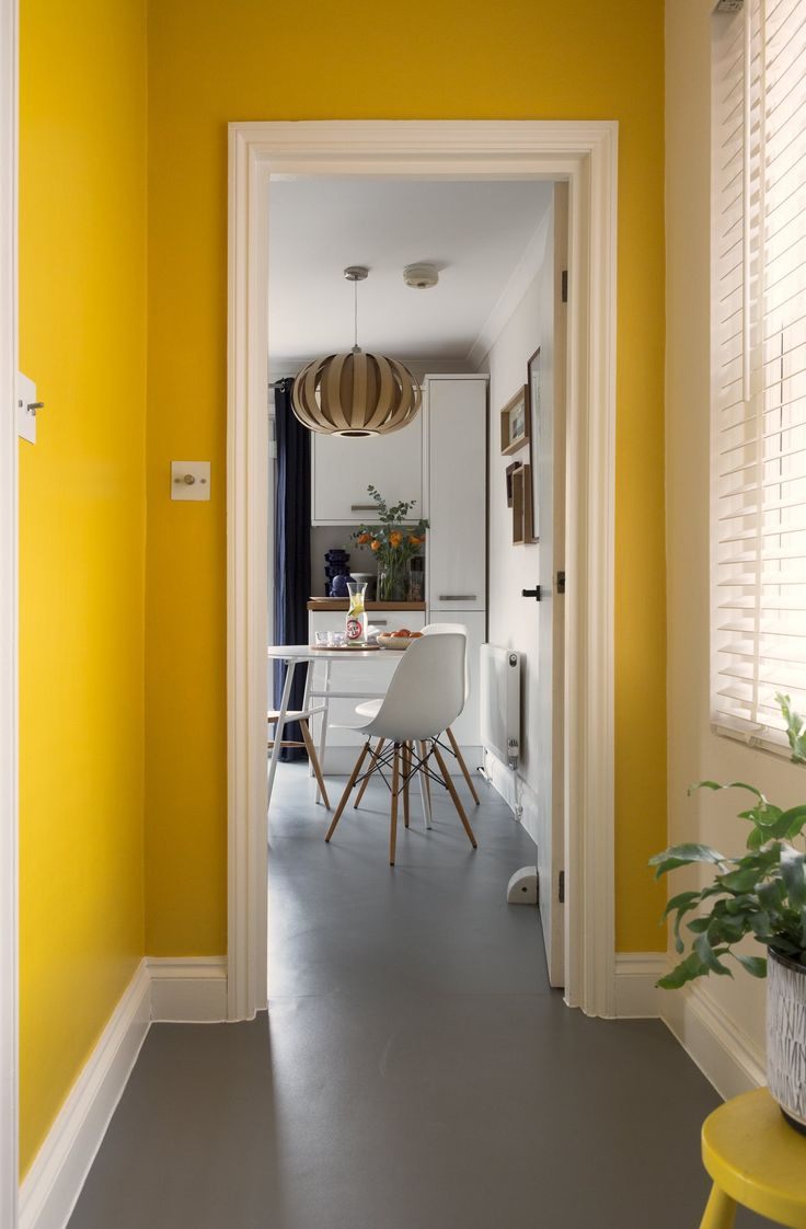 The vibrant yellow (Mister David by Little Greene Paint Company) frames the entrance to the kitchen.