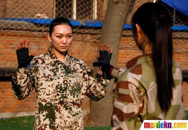 Calon Bodyguard wanita menggunakan senjata replika untuk berlatih melucuti senjata dari penyerang dalam sesi pelatihan di Beijing China.