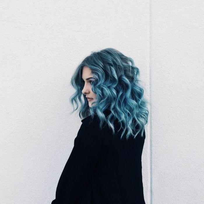 blaue, lockige Haare, schwarzer Mantel, Porzellanteint, dunkle Augenbrauen, matte Lippen