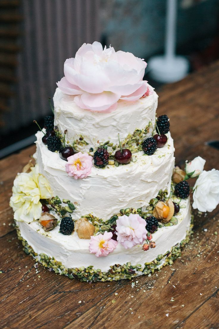 3 tier, layered pistachio and rosewater with butter cream icing wedding cake -  Image by Lee Robbins Photographic - David Fielden Wedding Dress & Jimmy Choo Shoes for an urban, industrial wedding at MC Motors London City with pastel bridesmaid gowns & Groom in a Vivienne Westwood Suit.