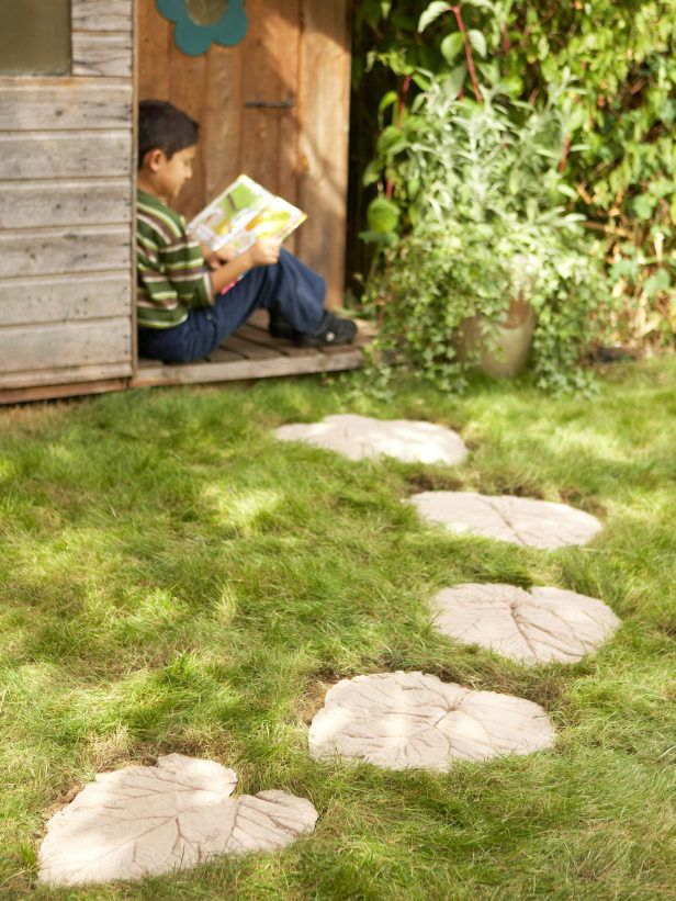 Concrete leaf stepping stones lead the way to a backyard playhouse.