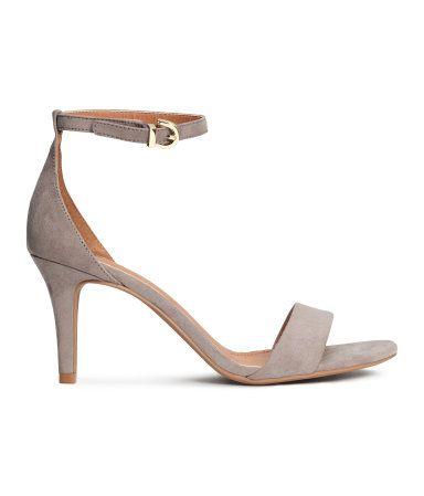 Sandaletten mit bezogenem Absatz und elastischem Knöchelriemen mit Metallschnalle. Futter und Innensohle aus Lederimitat. Absatzhöhe 8 cm. Gummisohle.