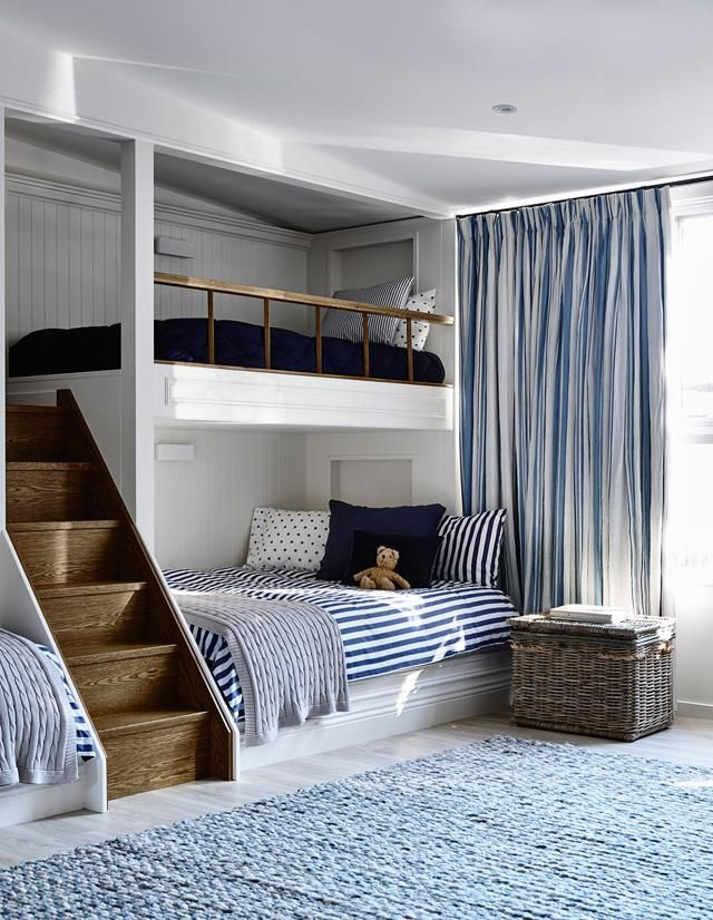 """In a home on Victoria's Mornington Peninsula, a garage has been converted into a multi-use room with twin sets of single and double bunks built in along one wall. The owners wanted to comfortably accommodate visiting family members, says interior decorator Adelaide Bragg. """"The steps are a favourite feature for their grandchildren."""" Shipshape joinery and soft furnishings in crisp navy and white play along with the coastal styling of the home."""
