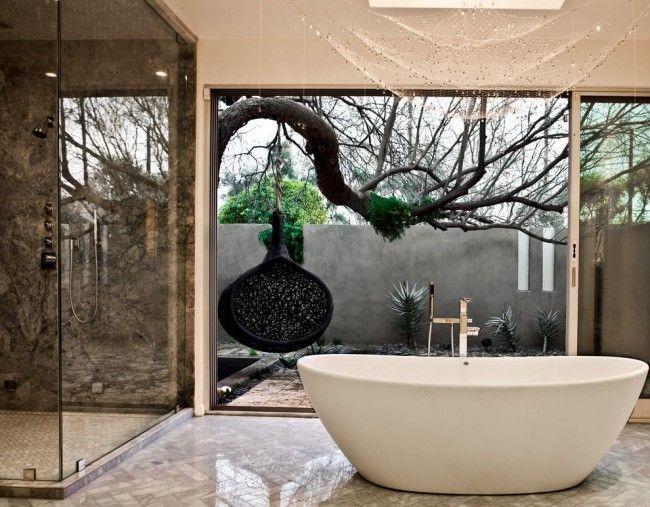Черная круглая качель, подвешенная на дереве, идеально вписывается в интерьер сада и дополняет невероятный вид из панорамного окна ванной, хоть участок и глухо закрытый