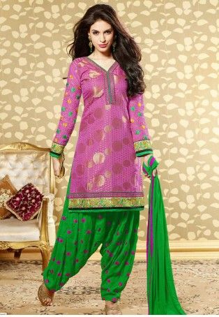 Banarasi Jacquard Knee length straight cut Kurta in full sleeves woven in golden polka dots is embellished with resham and Zari embroidered panel on the hemline and sleeve ends and embroidered with floral motifs on the sleeves. It is coordinated with a Bright green Salwar with magenta motifs and chiffon dupatta.