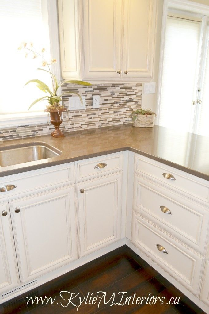 kitchen cream of white and glazed cabinets, small mosaic tile backsplash and dark wood floors with brown quartz countertops