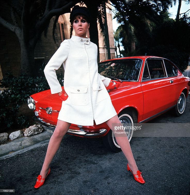 British actress Joanna Lumley poses by a red Fiat 850 Coupé as she models a white coat worn with red shoes and matching gloves, 1968.