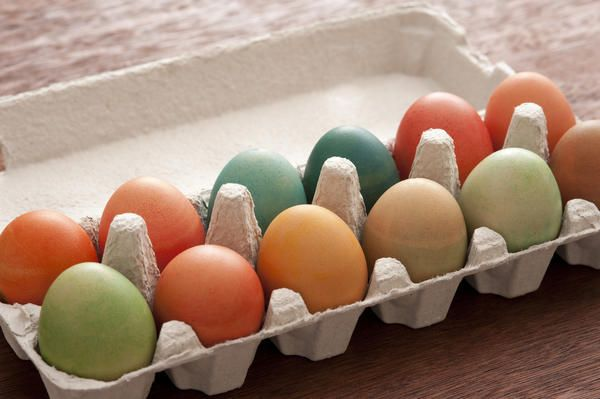 Love this image: Close-up carton box of dozen colorful dyed Easter eggs on dark table surface - By stockarch.com user: easterstockphotos