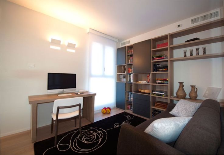 Un piccolo armadio con terminale a giorno crea l'effetto di un setto tra il living e lo studio. La libreria con terminale a mensole consente di posizionare sulla parete adiacente il divano letto fungendo da comodino. Le luci integrate nella parete sviluppano una luce diffusa calda.