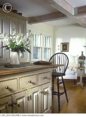 Love everything about this room.  Early American style. Distressed 'museum finish' cabinets. Windsor back bar stool. White wing back chair in background