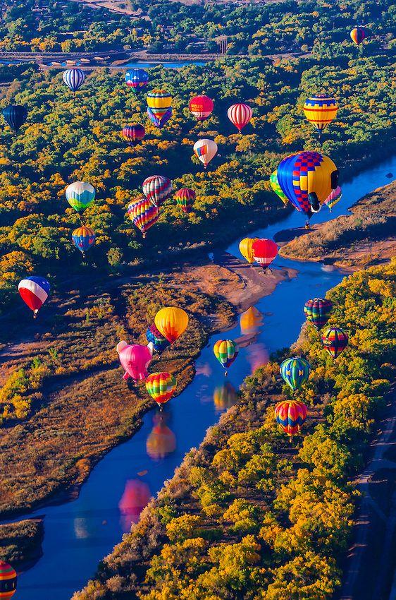 Hot air balloons flying low over the Rio Grande River just after sunrise, Albuquerque International Balloon Fiesta, Albuquerque, New Mexico ...