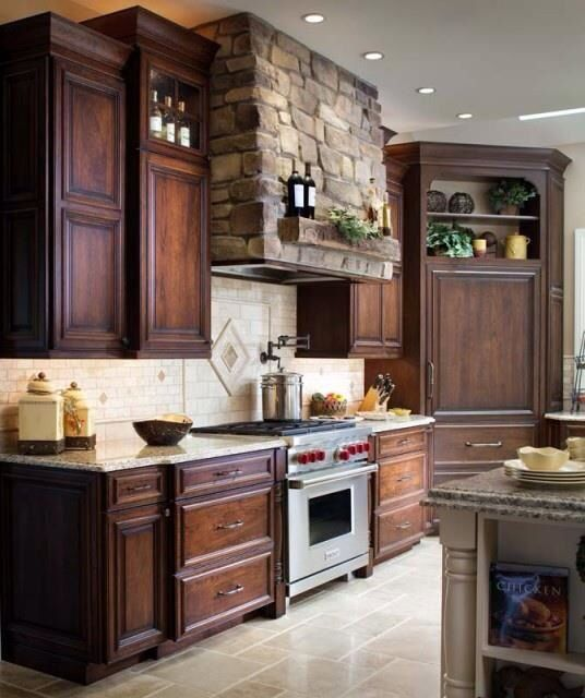 love the stone range hood and the dark wood cabinets mix with cabinets