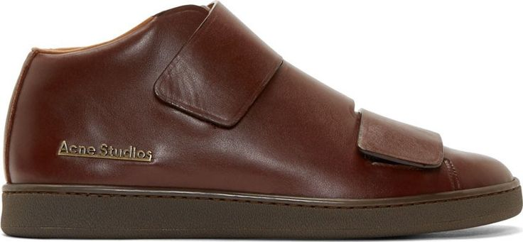 Mid-top soft leather sneakers in brown. Round toe. Three Velcro strap closure at vamp. Tarnished brass logo embellishment at side. Textured rubber sole in brown. Tonal stitching.