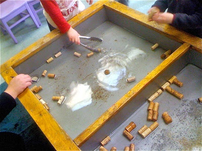 "Corks & tongs in the water tray ("",)"