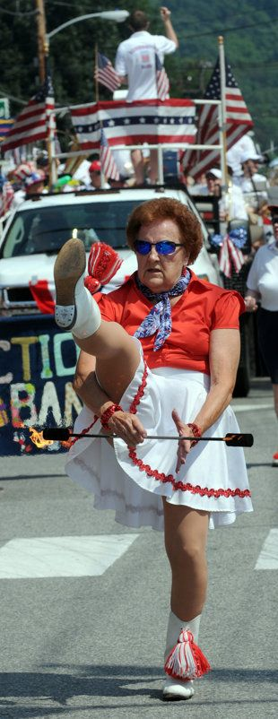 """Majorette Betty Lambert leads the Resurrection Band, twirling batons between her legs and above her head, and stopping several times along the route to perform the splits. The 79-year-old recently gave up cartwheels but still twirls knives, and fire-batons when it isn't windy."""