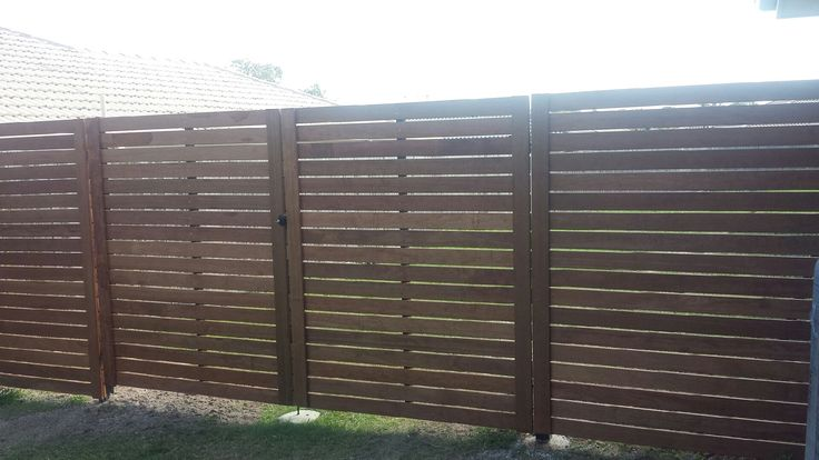 This a fence made from horizontal merbau decking on black powder coated steel posts.
