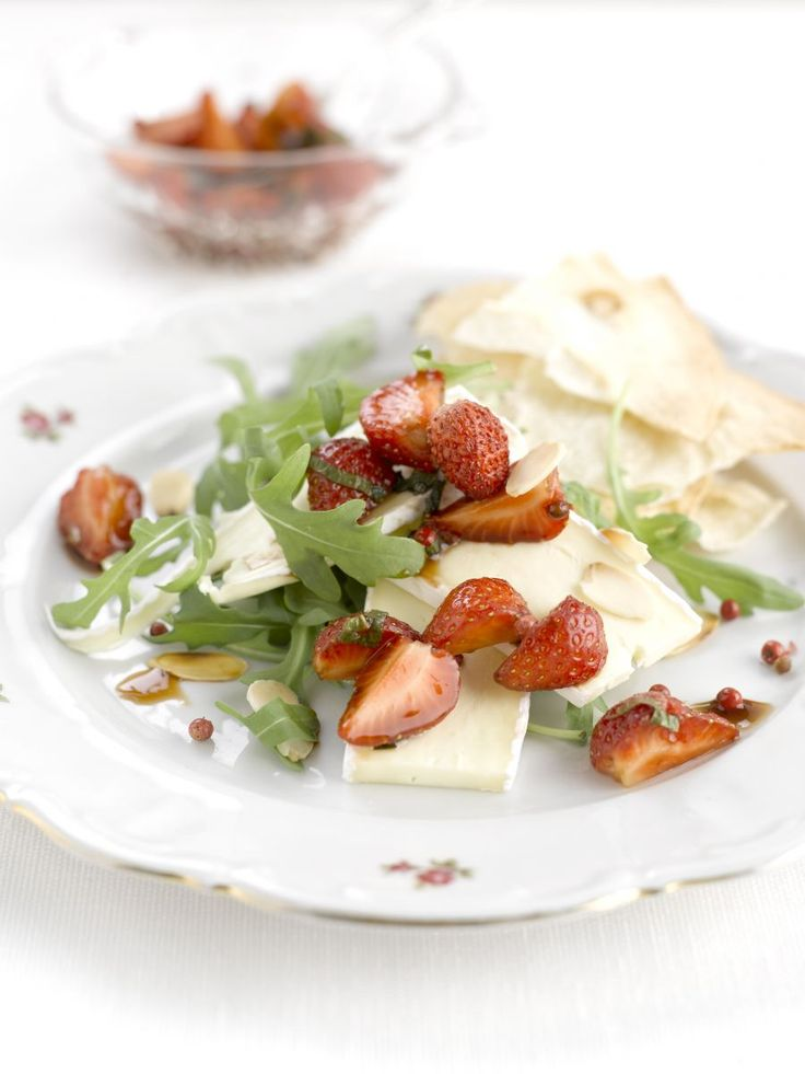 1 dag van tevoren:Maak een marinade van de honing, balsamico, de helft van de roze peperbolletjes en de helft van de citroenmelisse. Schep er de aardbeien door, dek af en laat een nachtje marineren. Bereiden: Laat de aardbeien uitlekken en bewaar de marinade. Klop die met de slaolie en de rest van de peperbolletjes tot een dressing. Verdeel de rucola, brie en aardbeien over vier borden en besprenkel met de dressing.Serveren: Werk af met geroosterde amandelen.