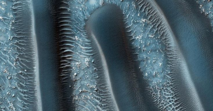 """Dunas de areia estão entre as características eólicas mais comuns presentes em Marte. A distribuição espacial e morfológica das dunas muda de acordo com a circulação e força dos ventos. Com a curadoria de artistas, fotógrafos e editores de fotografia, a Nasa reuniu uma série de imagens para compor a """"exposição online"""" chamada de """"Marte como Arte"""""""