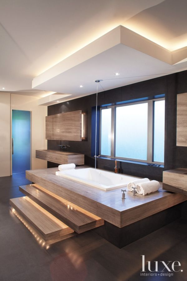 His-and-hers sinks in the spa-like master bath were built on-site from eight-foot-long pieces of solid granite and are each anchored by four unseen cantilevered columns. Floating steps of granite, which are indirectly lit with LEDs, lead up to a whirlpool MTI tub.
