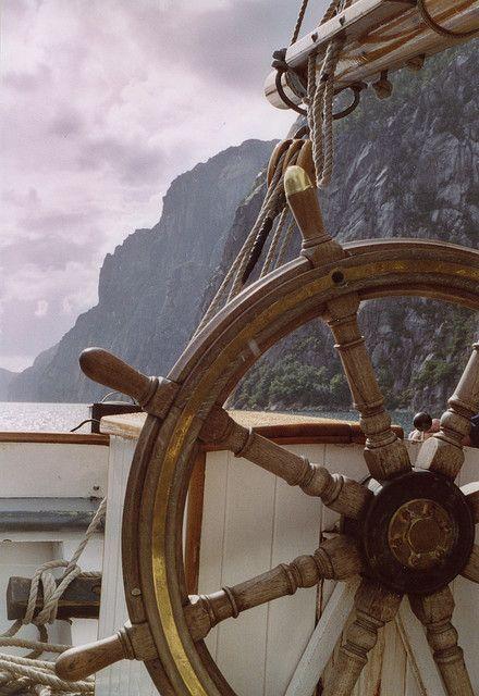Bessie Ellen's Wheel & Lysefjord cliffs    Sailing close to sheer cliffs in Norway's Lysefjord. Bessie Ellen is a elegant west country trading ketch built in 1904 and restored by owner Nikki Alford.