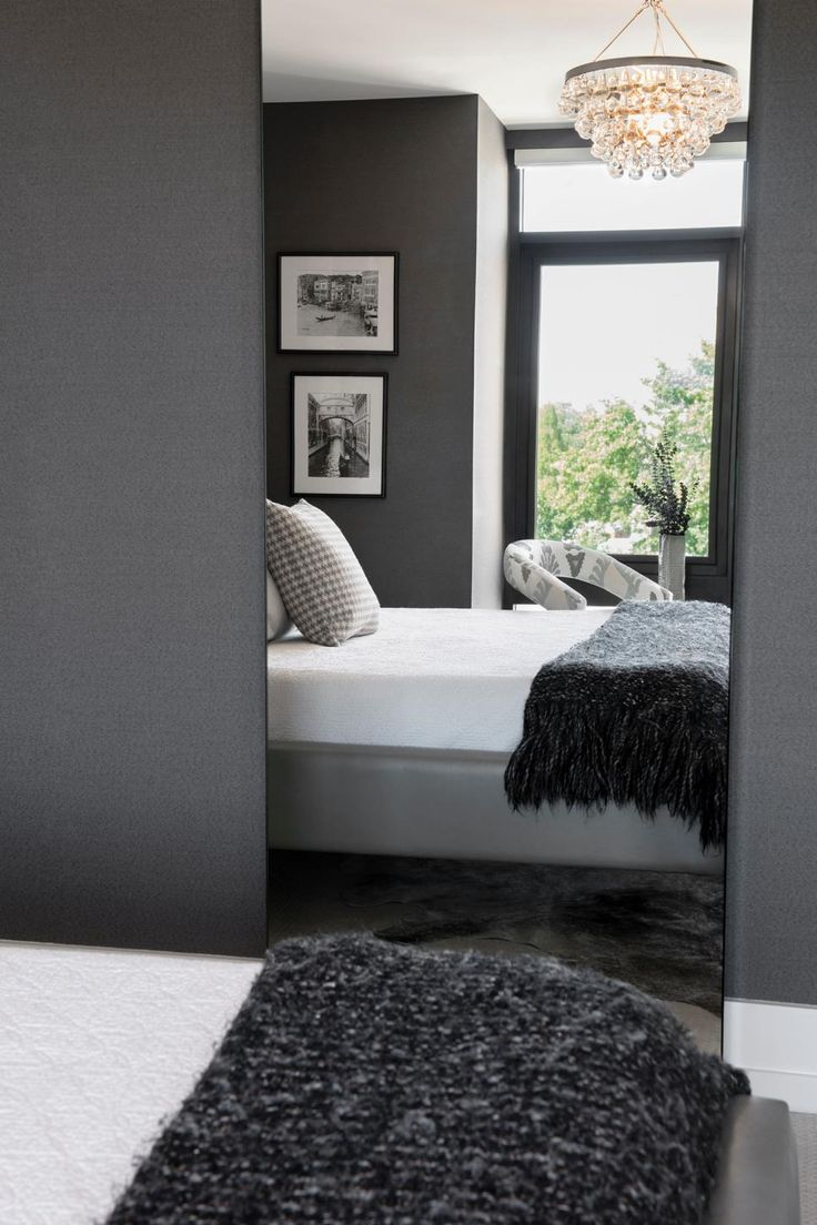 A tall, frameless mirror carries the reflection of this modern gray master bedroom to make it appear larger. An elegant chandelier adds a sophisticated look to the small space.