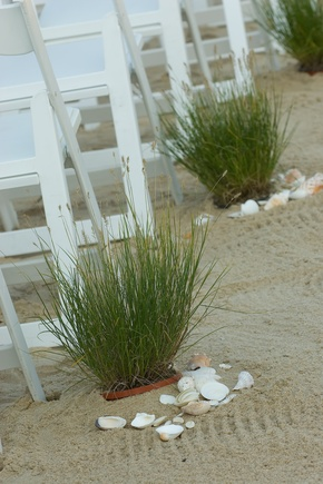 Love this! beach wedding aisle decor... potted grass buried in sand