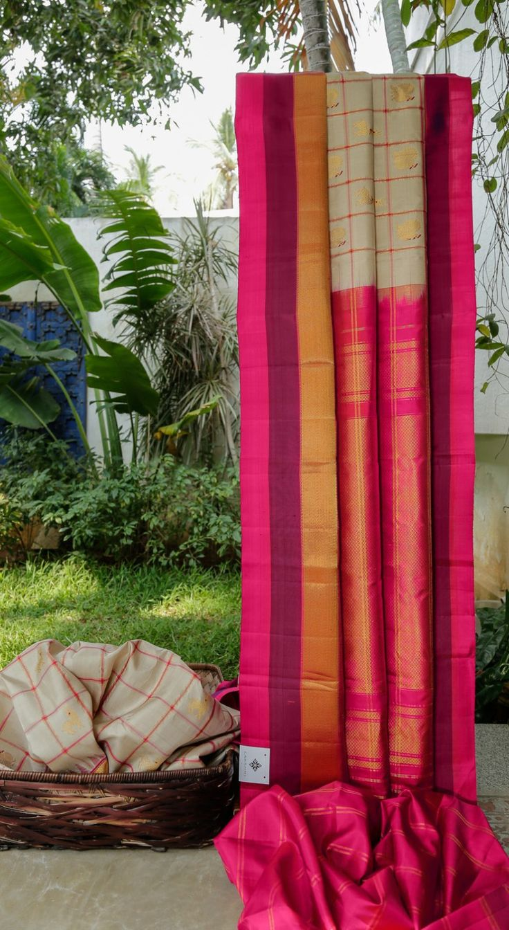 This gadwal silk is in white chequered with magenta and gold zari and has gold zari bhuttas in between squares with red thread work. the border is in magenta and violet with gold zari. the pallu is…