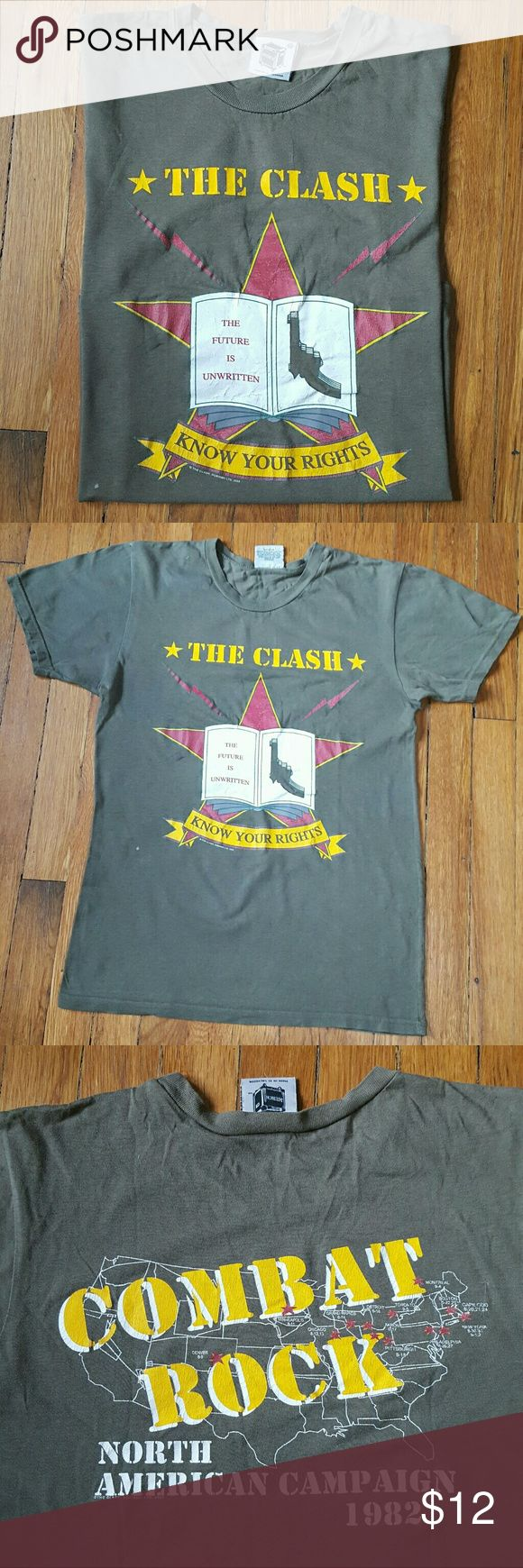 """The Clash Combat Rock Tour T-Shirt The Clash Combat Rock Tour T. This is a 2005 reprint, *not* original. It is in lightly distressed condition- some piling, cracking on the graphic and small stains- mostly paint. 100% cotton. Marked XS, 17.5"""" armpit to armpit, 26"""" top to  bottom. Color is a little more army green and less grey than it looks in the photos. Shirts Tees - Short Sleeve"""