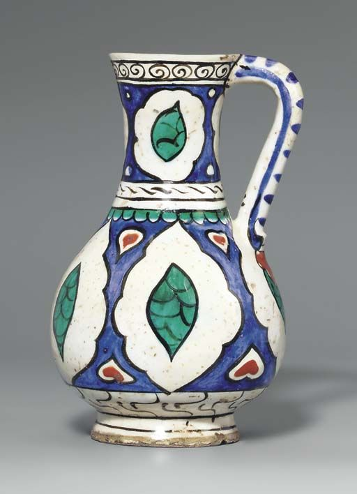 AN IZNIK POTTERY JUG OTTOMAN TURKEY, CIRCA 1620 Of slender baluster form on short foot with flaring trumpet mouth & simple loop handle, decorated in cobalt-blue, bole-red, green & black beneath the clear glaze with five white ogival cusped cartouches containing ovoid panels of green fish-scale reserved against the blue ground, small heart-shaped white & red cartouches in the interstices, a band of black & white stylized marbling along the base, double white band with green fringe 8 1/8in.