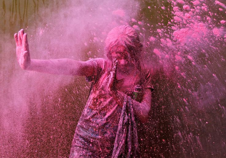 An Indian woman shakes her head covered in colored powder during Holi in Mumbai, India