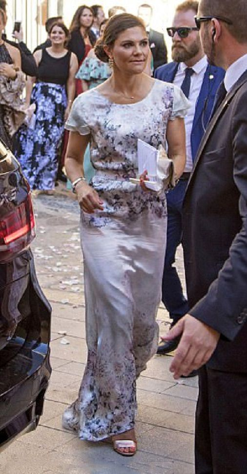 Crown Princess Victoria of Sweden, who is heiress to the Swedish throne, wore a sweeping cream dress with an elaborate floral pattern, holding a fan to keep cool in the Spanish heat as she attends for the nuptials of her cousin's Helena Christina Sommerlath and Ian Martin at Palma de Mallorca Cathedral on August 5, 2017