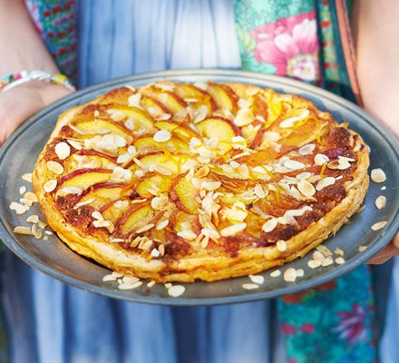 Top puff-pastry with sliced peaches to make this rustic, simple Spanish-style fruit tart - an easy yet attractive dinner party dessert