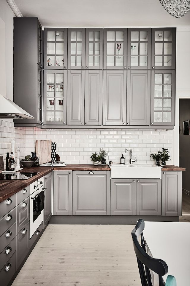 The kitchen design is great in this Swedish apartment, the beautiful shade of grey for the cabinets, the bevelled subway tiles and warm wood counters, plus the double butlers sink. Love the combinatio