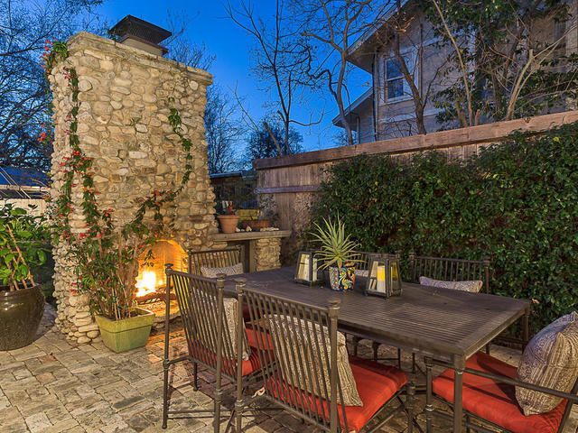 An outdoor fireplace with stone chimney and outdoor dining set.