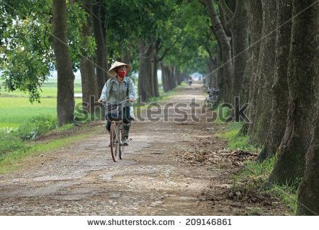 HANOI, VIETNAM - JUL 13, 2014: Unidentified Asian woman cycling on a country…