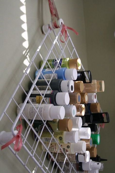 Perfect. She used two shelves from one of those wire shelving units and zip tied empty thread spools in all four corners and the middle. Have to do this. I have some grid squares in the closet and about a billion Plaid acrylic paint bottles. Put a dot of paint on the lid of each and finding the right color is a snap. Also, maybe I will stop buying colors I already have.