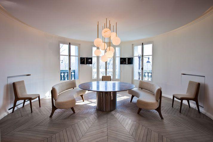 A Modern Apartment Near The Eiffel Tower | Yatzer Suspension composee de globes en Pierre foussana ( ateliers Illouz) . Autour, banquettes et chaises a la manicure de Kagan . Parquet en point de hongrie , restaure decape et lasure de Gris .