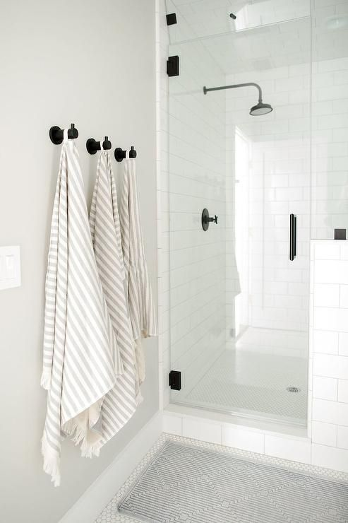 Oil Rubbed Bronze Towel Hooks Are Mounted To A Light Gray Wall Over Bath Mat Placed On White Hex Floor Tiles Outside Of Seamless Gl Shower