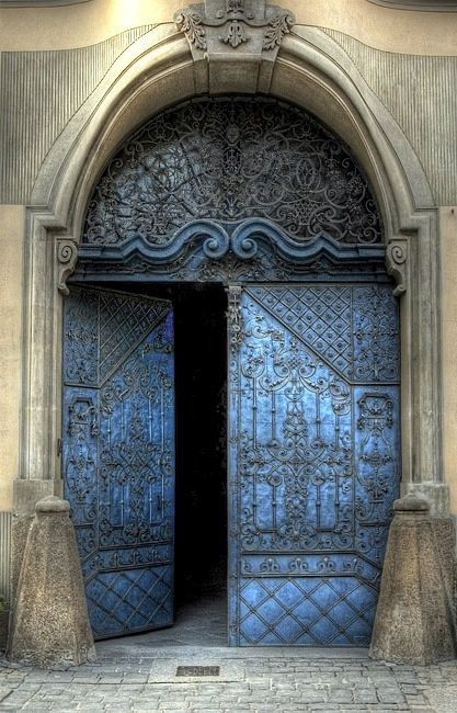 I appreciate the way that the doors are set inside the arch, but I wish that the arch would also be included in the swinging mechanisms of the door. The curving, organic ornamentation is very interesting as well.  The blue color seems to be common in doors- there's at least one other door with this color scheme.